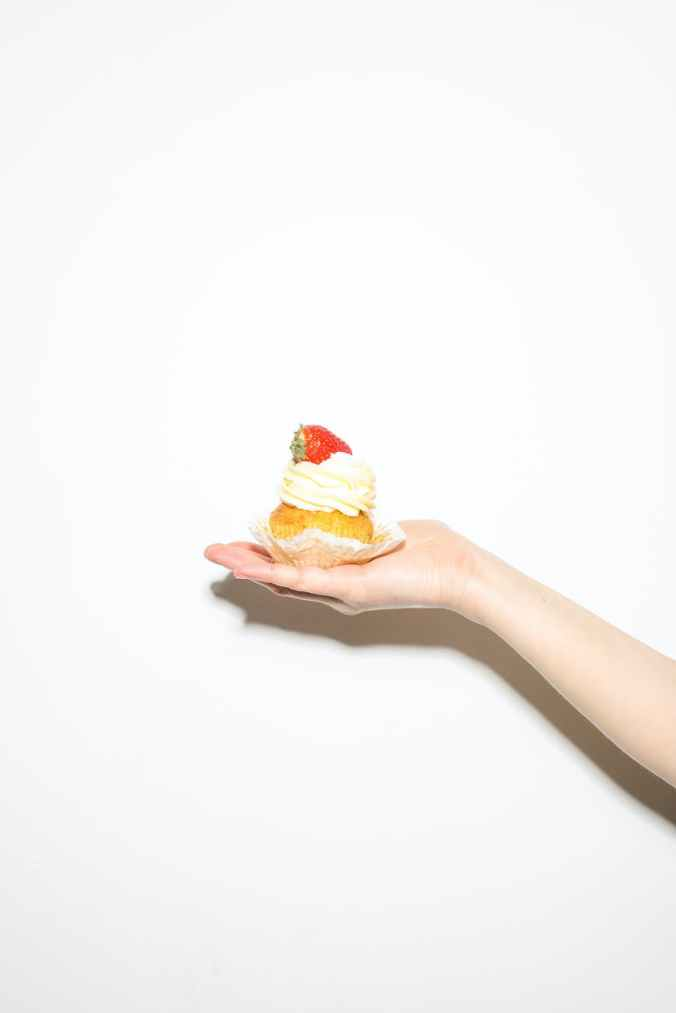 photo of person holding cupcake