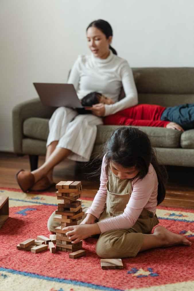 mother working on laptop near cute kids
